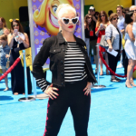 """Christina Aguilera attends """"The Emoji Movie"""" premiere on July 23 in Westwood, CA, walking the blue carpet in a pair of Saint Laurent 'Lou Lou' heart shape sunglasses, Saint Laurent striped top and Gianvito Rossi Rossi Porto black and red Sandals."""