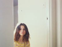 Selena Gomez poses in a pale pink and yellow Simone Rocha Floral Embroidered Frill Dress for a promotional shoot for her latest single Fetish.