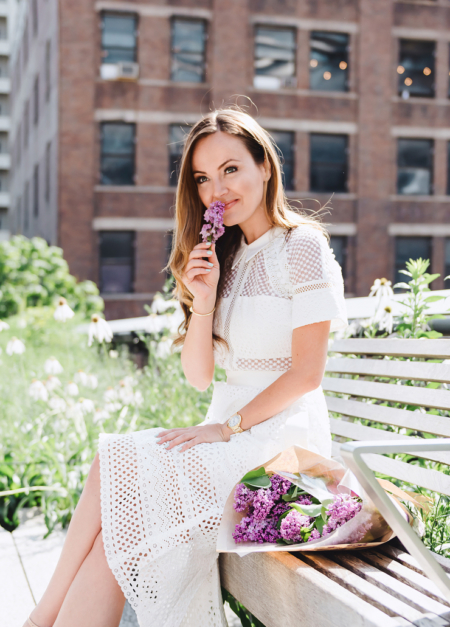 "Nicole Lapin posted this photo to her Instagram (July 2) with the caption ""I would spend my last $10 on old books and fresh flowers."" She is wearing a 50's style Self-Portrait Broderie Anglaise Cotton Midi Dress."